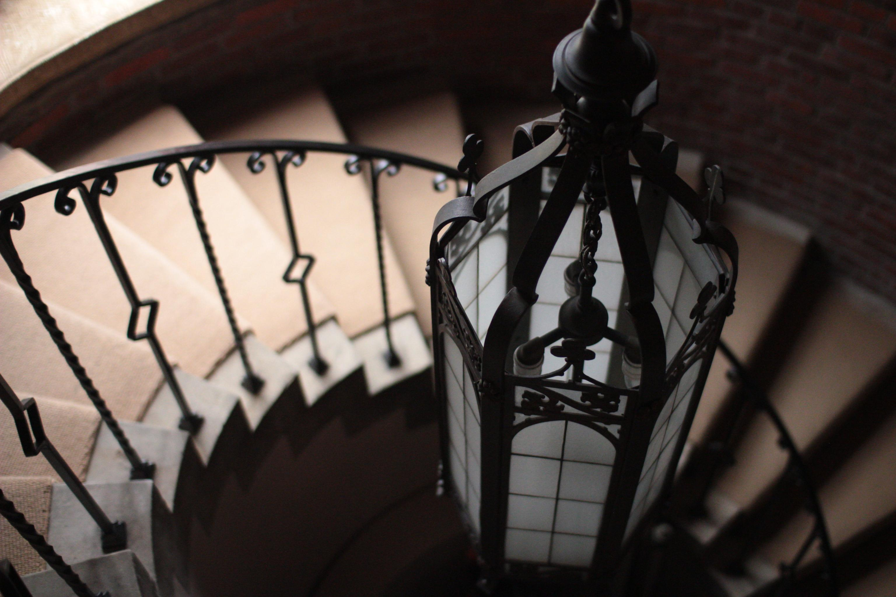 photo of a lamp suspended over a spiral staircase