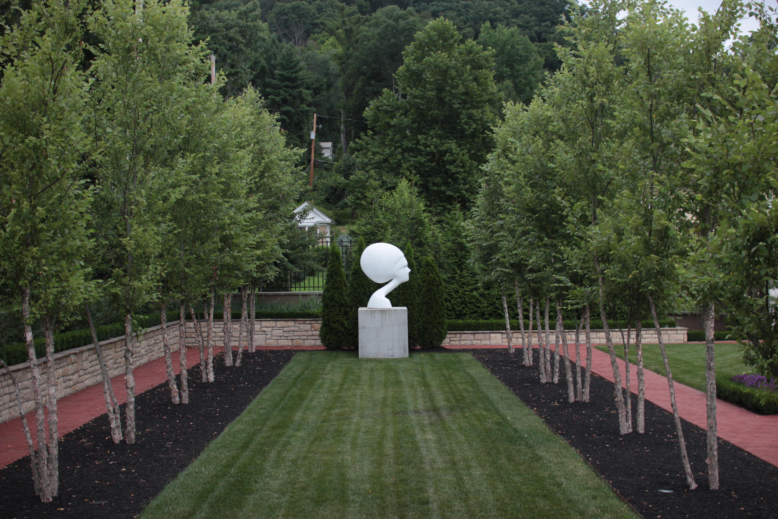 photo of a head sculpture at the end of a strip of grass, between two rows of trees