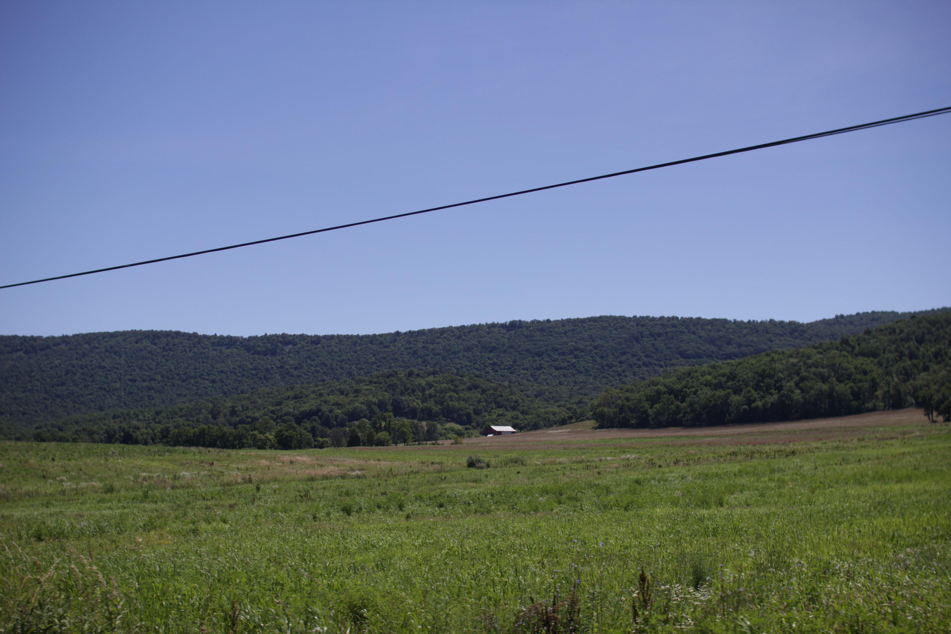 fields with distant rolling hills, a small house, a powerline cutting across the view